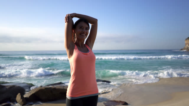young woman standing on yoga mat stretching her arms next to the beach smiling - stretching stock videos & royalty-free footage
