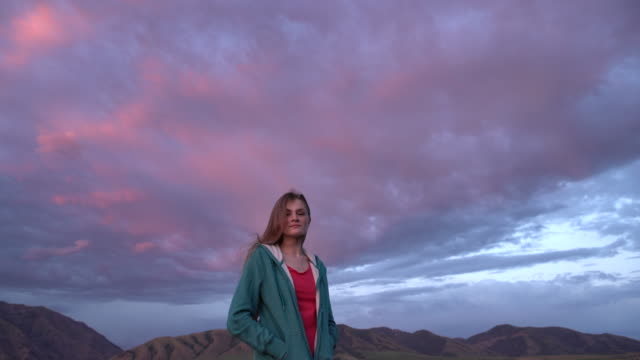 WS young woman standing outside under a big cloud at sunset