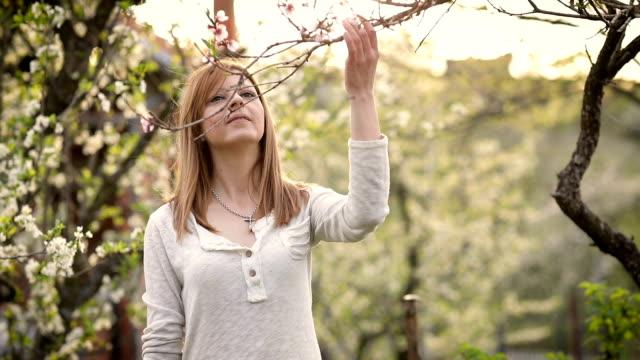桜の木に立っている若い女性 - 四月点の映像素材/bロール