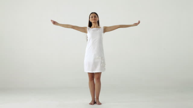 Young woman standing with her arms outstretched