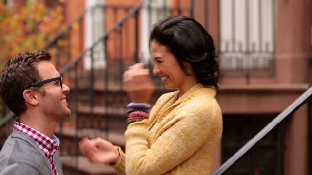 young woman stands above boyfriend on brownstone stoop, playfully putting glasses on him and kissing him on forehead - forehead stock videos and b-roll footage