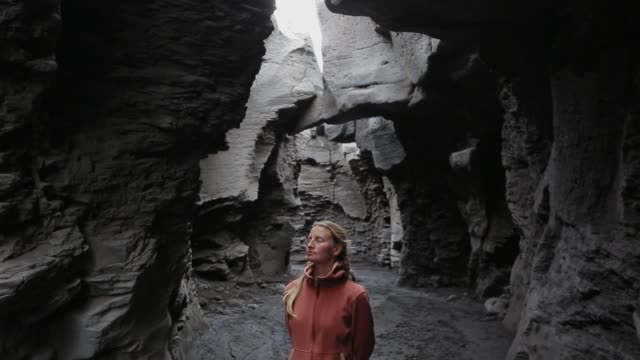 A young woman stands in a stone gorge