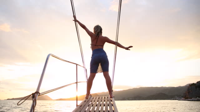 Young woman stands on boom of sailing ship, looks off
