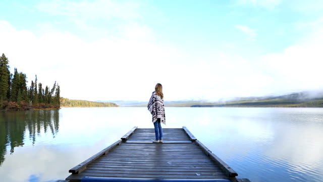 Young woman stands on wooden pier