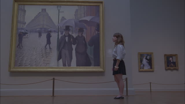 vídeos de stock, filmes e b-roll de a young woman stares at a large painting in the chicago museum of contemporary art in chicago, illinois. - encarando