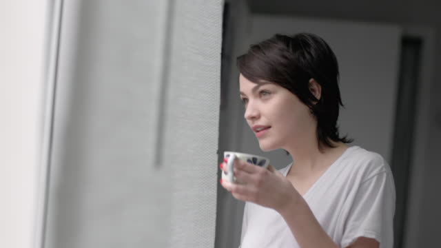 Young woman stares out bedroom window drinking coffee, looks back at boyfriend in bed and smiles