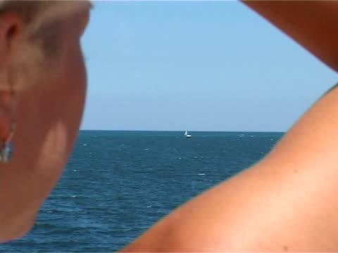 vidéos et rushes de jeune femme regardant voile sur un yacht afar - seulement des jeunes femmes
