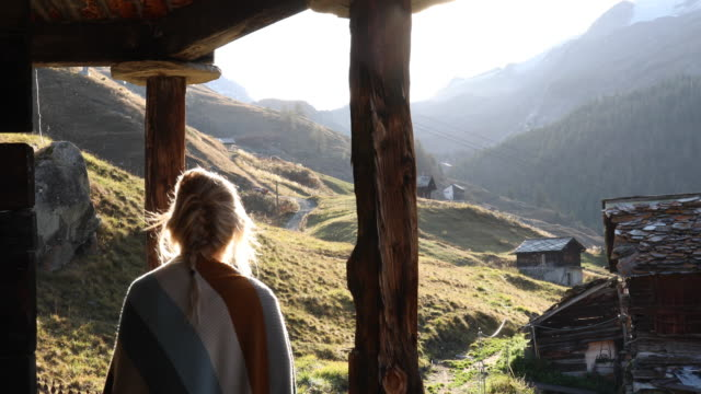Young woman steps onto chalet veranda with hot drink