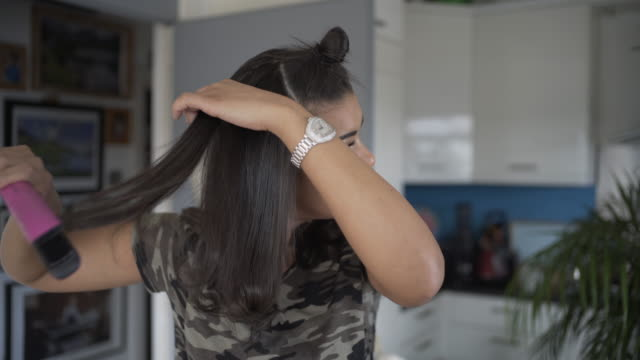 vidéos et rushes de a young woman straightening her hair. - hair straighteners