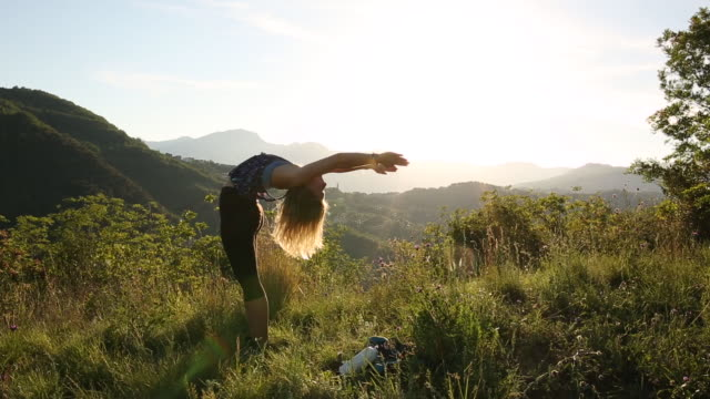 young woman stretches in green meadow during hike - inarcare la schiena video stock e b–roll