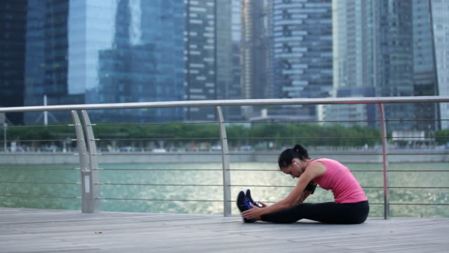 WS Young woman stretching after a workout in the city.