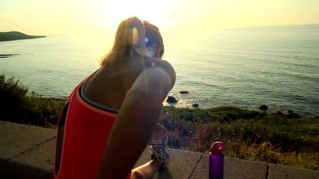 stockvideo's en b-roll-footage met jonge vrouw stretching na het joggen buiten - middellandse zee