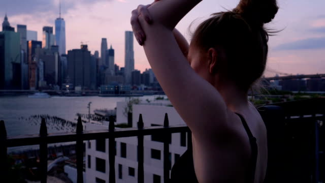 Young woman stretching against the New York City waterfront sunset