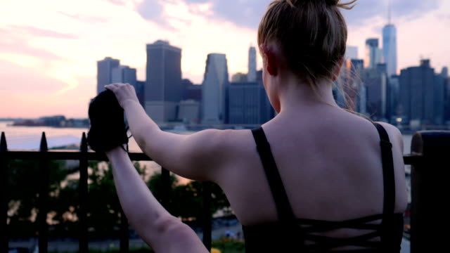 young woman stretching against the new york city waterfront sunset - fare lo stretching video stock e b–roll