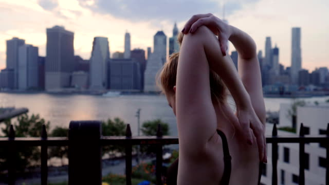young woman stretching against the new york city waterfront sunset - coda di cavallo video stock e b–roll