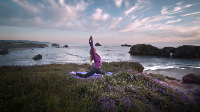 vídeos de stock e filmes b-roll de young woman stretching and doing yoga at scenic view of ocean at sunset, oregon - linha do horizonte sobre água