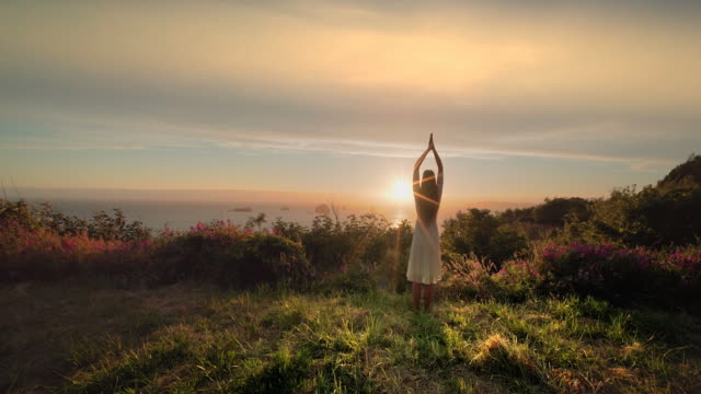 Young woman stretching and doing yoga at sunset overlooking Pacific Ocean