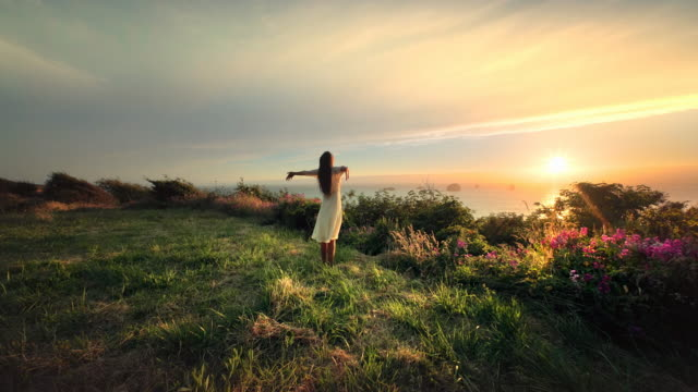 stockvideo's en b-roll-footage met young woman stretching and doing yoga at sunset overlooking pacific ocean - mindfulness