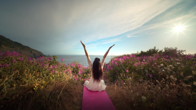 vídeos de stock, filmes e b-roll de young woman stretching and doing yoga in field of flowers overlooking pacific oceann - rosa cor