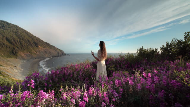 vidéos et rushes de young woman stretching and doing yoga in field of flowers overlooking pacific ocean - téléviseur ultra haute définition