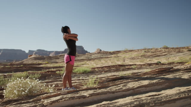 ws ds young woman stretching and jogging in desert landscape / lake powell, utah, usa - lake powell stock videos & royalty-free footage