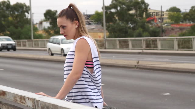 young woman stretching at the side of the road - maglietta senza maniche video stock e b–roll