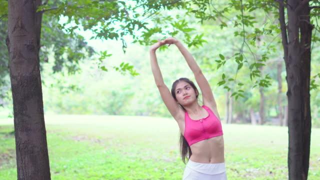 Jonge vrouw die zich uitstrekt door yoga in de tuin