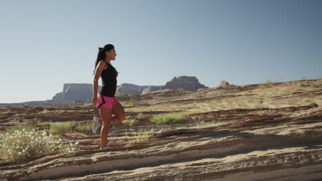 ws ds young woman stretching in desert landscape / lake powell, utah, usa - newoutdoors stock videos & royalty-free footage