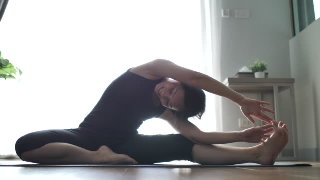 Young Woman stretching in living room at home