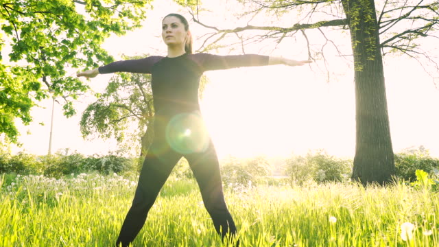 young woman stretching in nature. - serene people stock videos & royalty-free footage