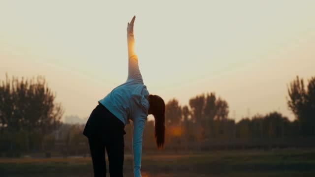 young woman stretching in the morning - 腕を広げる点の映像素材/bロール