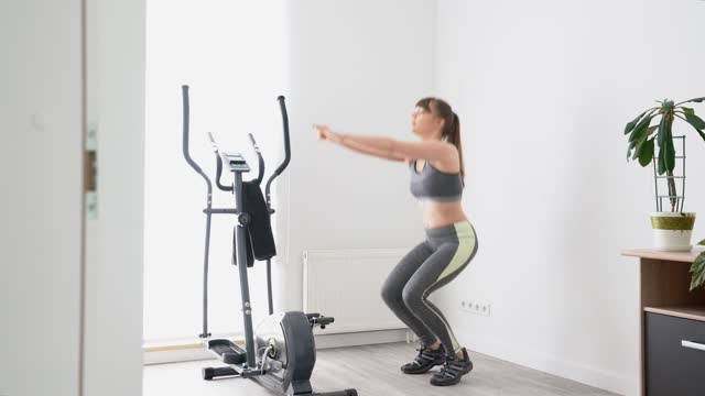 young woman stretching next to cross trainer at home - cross trainer stock videos & royalty-free footage