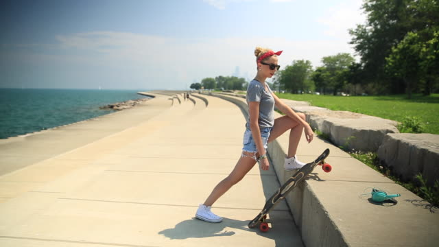 A young woman stretching next to her longboard skateboard.
