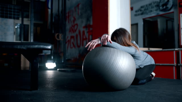 young woman stretching on a fitness ball - fitness ball stock videos & royalty-free footage
