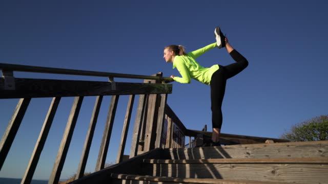 ms ts young woman stretching on a stairway - auf einem bein stock-videos und b-roll-filmmaterial