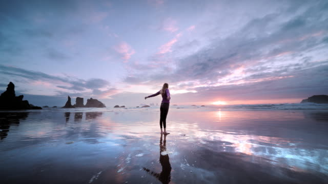 young woman stretching on beach at sunset, oregon - 静かな情景点の映像素材/bロール