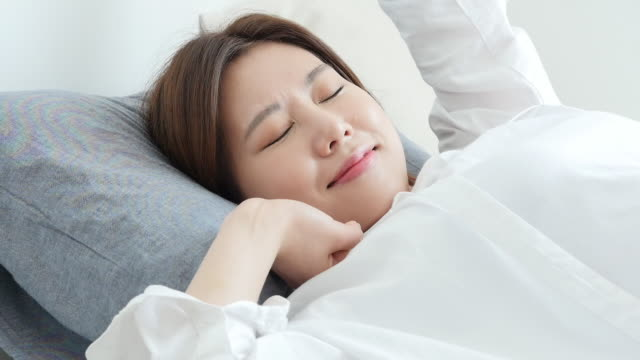 a young woman stretching on bed and enjoying single life - 人間の鼻点の映像素材/bロール
