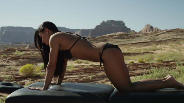 ms pan young woman stretching on massage table in desert landscape / lake powell, utah, usa - lake powell stock videos and b-roll footage
