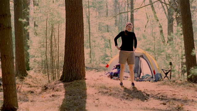 stockvideo's en b-roll-footage met ms, young woman stretching outside tent in forest (cross process), usa, pennsylvania, solebury - cross processen