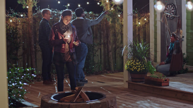 young woman strikes match to light fire pit while friends throw darts in the backyard. - terrazza in legno video stock e b–roll