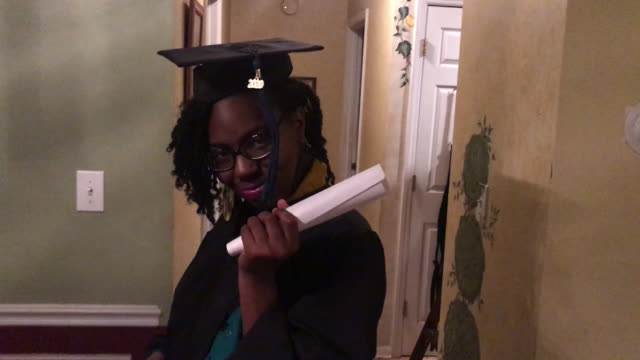 young woman struts down a hallway in her home for covid-19 graduation (audio) - graduation stock videos & royalty-free footage