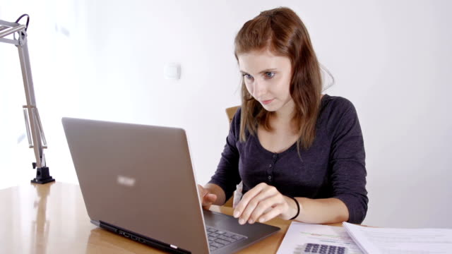Young woman studying and doing homework on her laptop