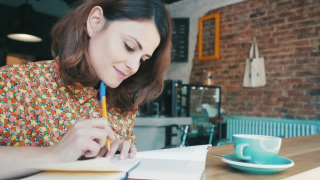 young woman studying in a coffee shop. - pen stock videos & royalty-free footage