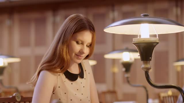 vídeos de stock e filmes b-roll de recipiente jovem mulher a estudar na biblioteca da sala de leitura - lâmpada elétrica