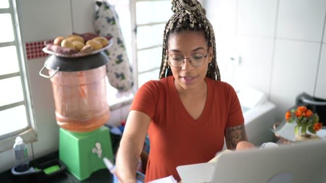 vídeos de stock, filmes e b-roll de jovem estuda com laptop em uma aula online em casa - 20 anos