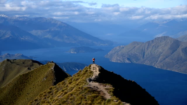 young woman success on the mountain summit , roy's peak , wanaka , new zealand - rucksack stock videos & royalty-free footage