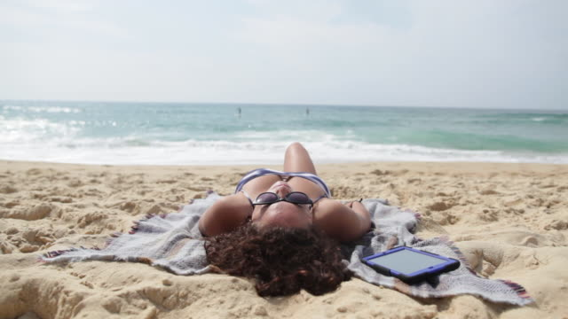 young woman sunbathing at the beach in the south of france. - sunbathing stock videos & royalty-free footage