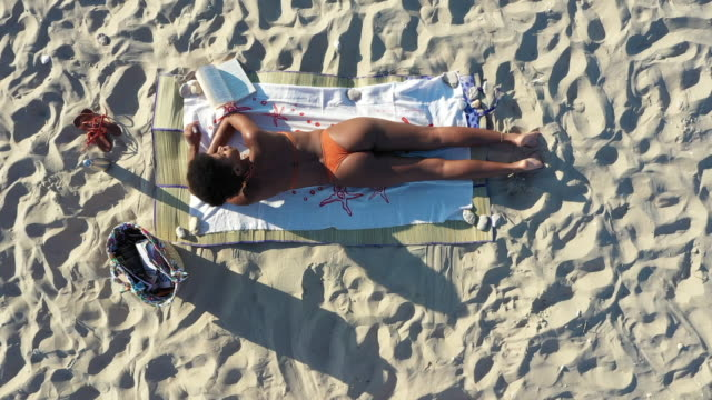 young woman sunbathing at the beach - sunbathing stock videos & royalty-free footage