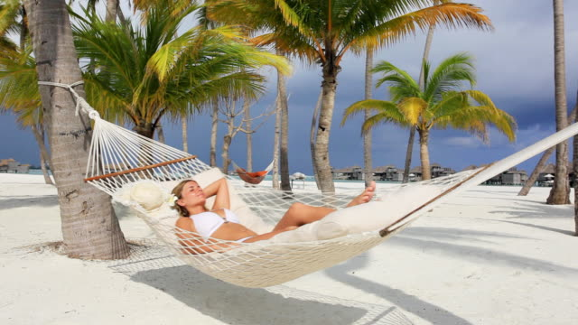 Young woman sunbathing in a hammock.
