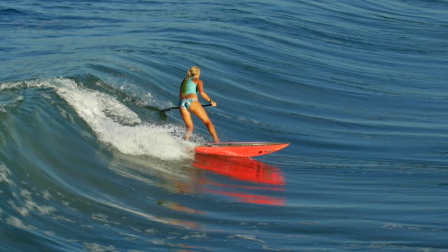 A young woman SUP surfing in a bikini on a stand-up paddleboard surfboard. - Slow Motion